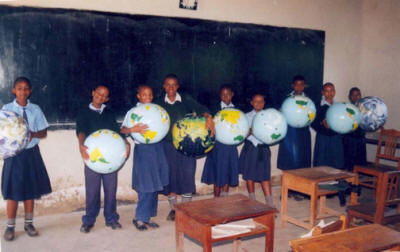 students holding inflatable globes in a classroom