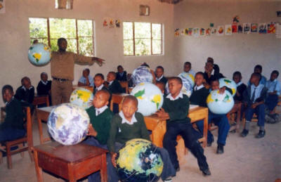 young students holding inflatable globes in a classroom